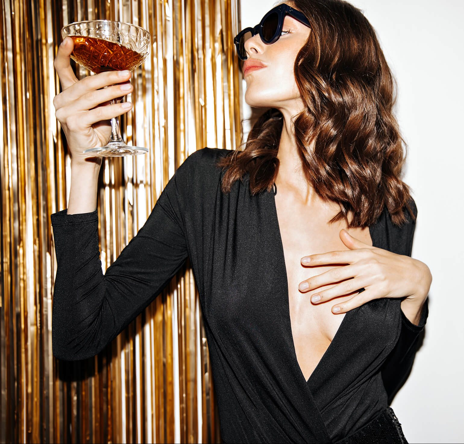 Woman in sunglasses with a cocktail