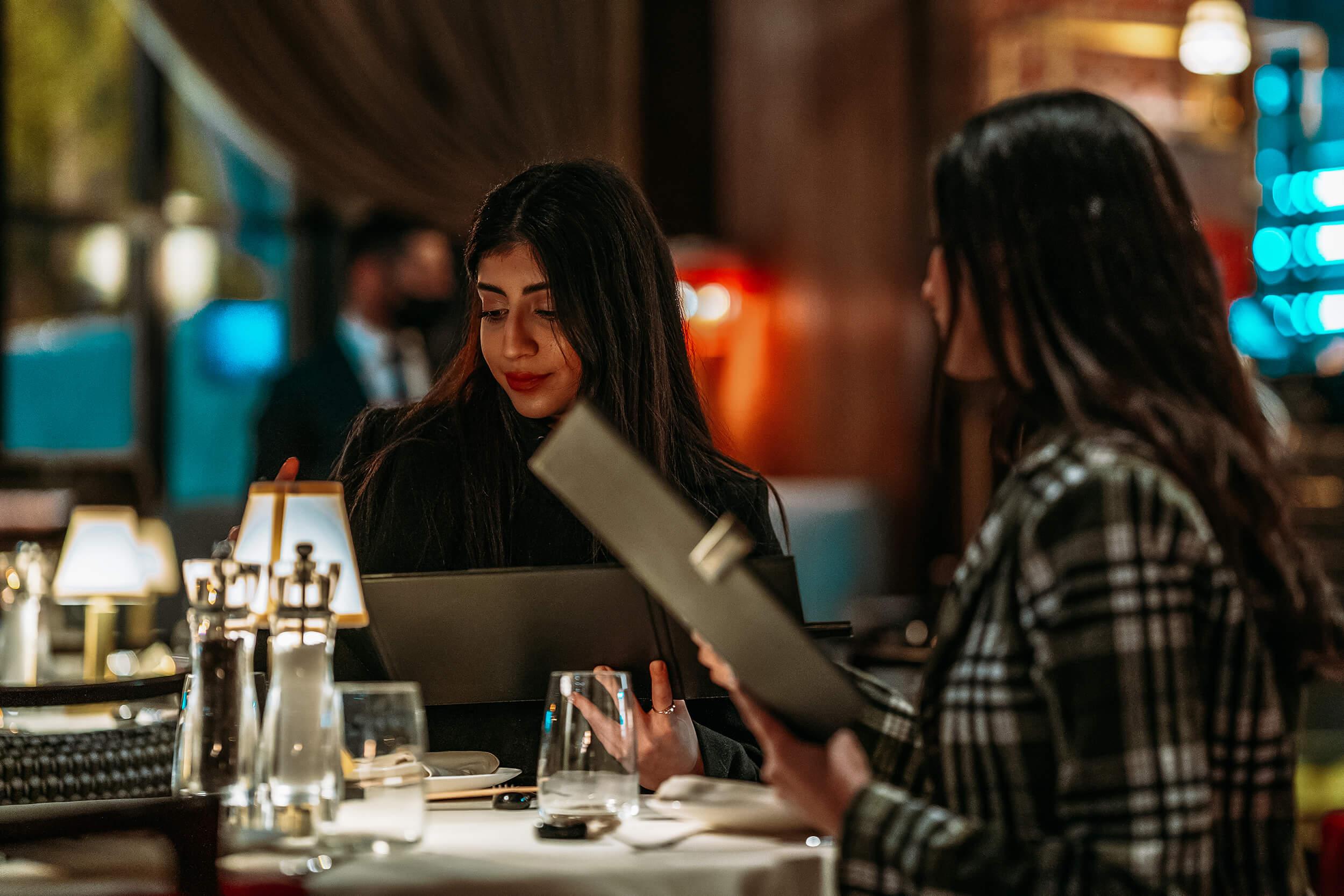 two women looking at menus